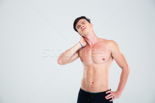 Portrait of a handsome man having neck pain Stock photo © deandrobot