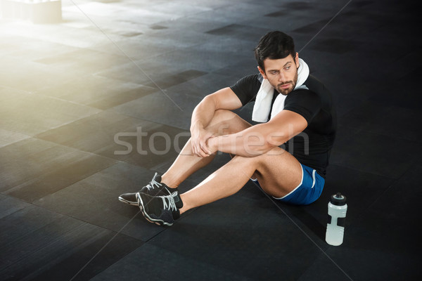 Sportsman sitting on the floor in gym Stock photo © deandrobot