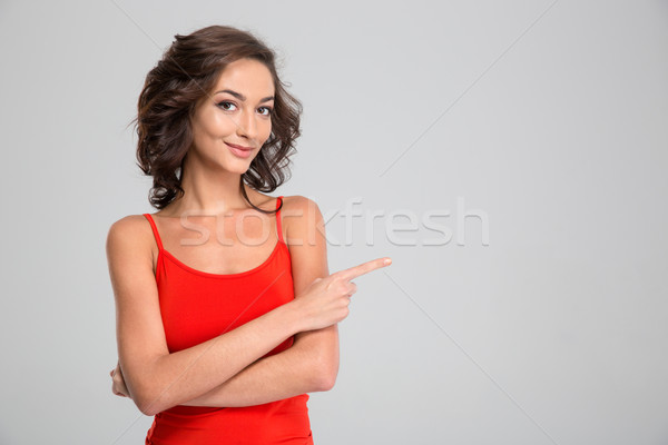Lovely pretty young woman standing and pointing away in copyspace Stock photo © deandrobot