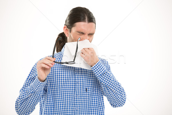 Young handsome man sneezing and using handkerchief Stock photo © deandrobot