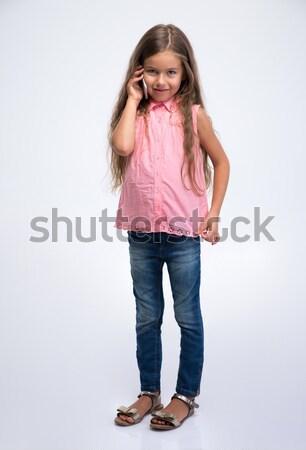 Stock photo: Full length portrait of a little girl talking on the phone