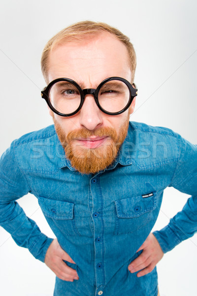 Angry amusing young man with beard in funny round glasses  Stock photo © deandrobot