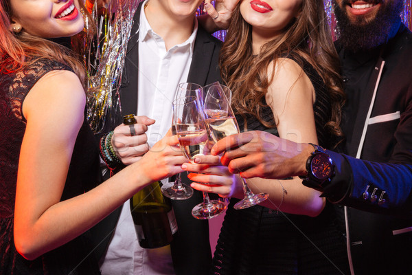 Bottle and glasses of champagne holded by happy young friends Stock photo © deandrobot