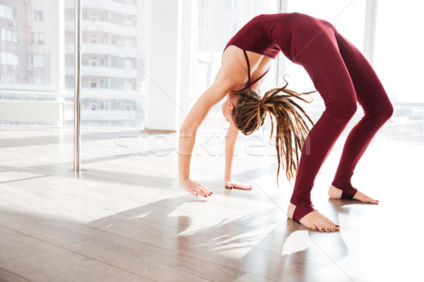 Beautiful young woman  bending and doing yoga in studio Stock photo © deandrobot