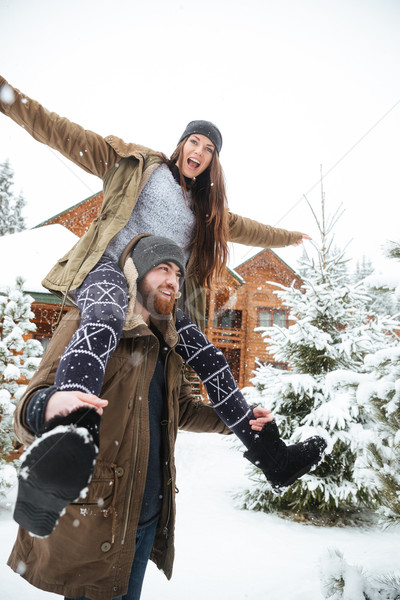 Smiling man carrying his girlfriend on shoulders in winter Stock photo © deandrobot