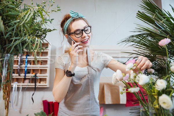 Woman florist talking on cell phone in flower shop Stock photo © deandrobot