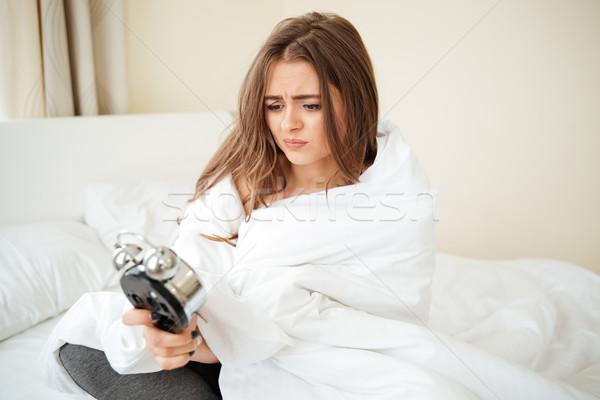 Infeliz mulher sessão despertador cama casa Foto stock © deandrobot