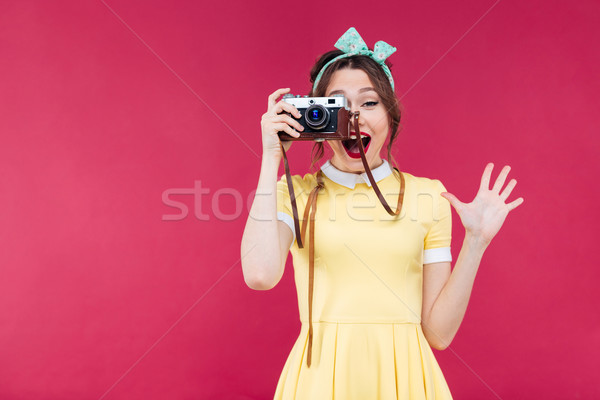 Happy pretty pinup girl taking pictures with vintage camera Stock photo © deandrobot