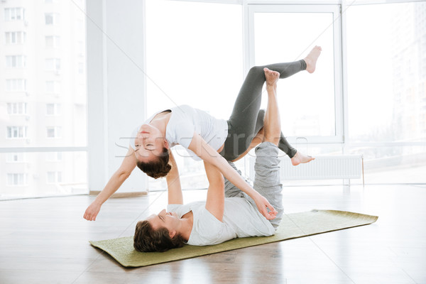 Relaxed couple practicing acro yoga exercises in studio Stock photo © deandrobot
