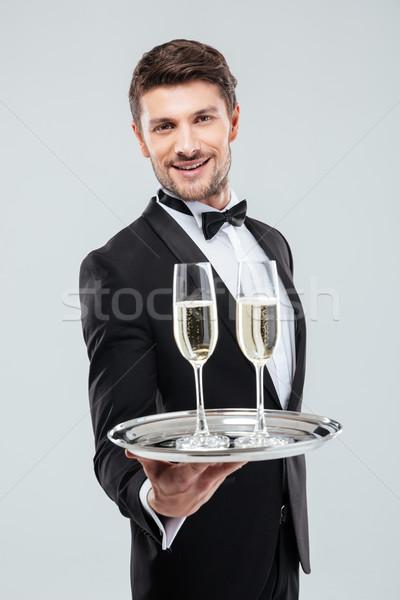 Sorridere giovani cameriere vetro champagne Foto d'archivio © deandrobot