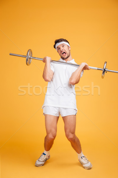 Full length of funny young fitness man holding heavy barbell Stock photo © deandrobot
