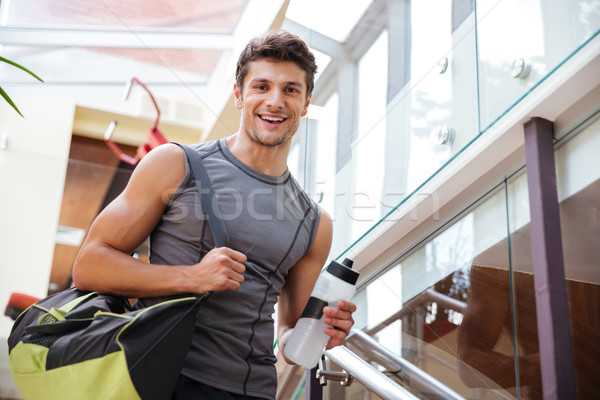 Cheerful fitness man with bottle of water walking on training Stock photo © deandrobot