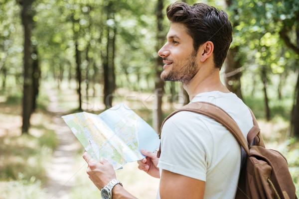 Man with backpack using map in forest Stock photo © deandrobot