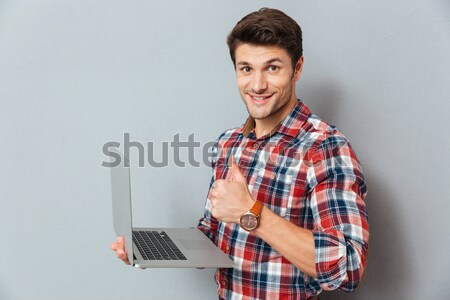 Handsome young man in plaid shirt using laptop Stock photo © deandrobot