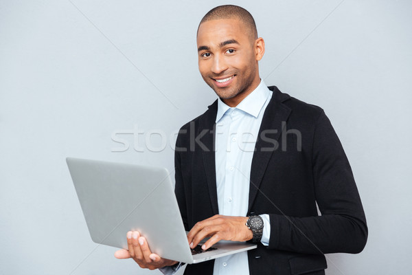 Boldog afroamerikai fiatalember tart laptopot használ mosoly Stock fotó © deandrobot