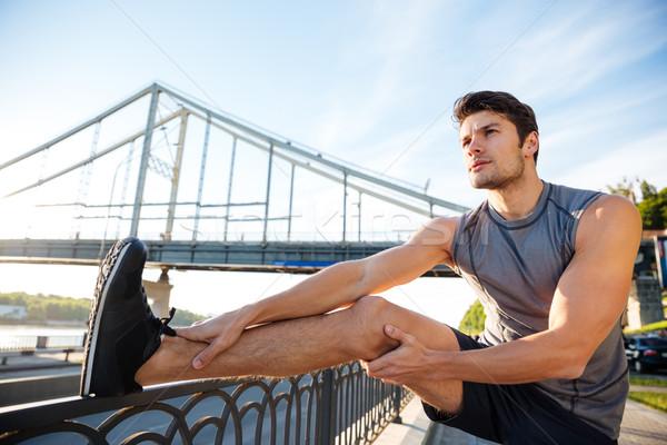 Sportok férfi nyújtás dől híd korlát Stock fotó © deandrobot