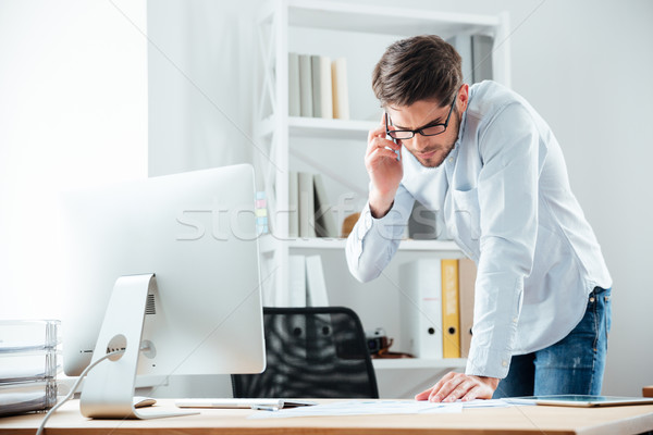 Business man standing at desk working on documents with mobilephone Stock photo © deandrobot