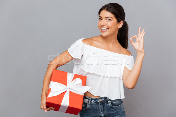 Smiling casual woman holding gift box and showing okay sign Stock photo © deandrobot