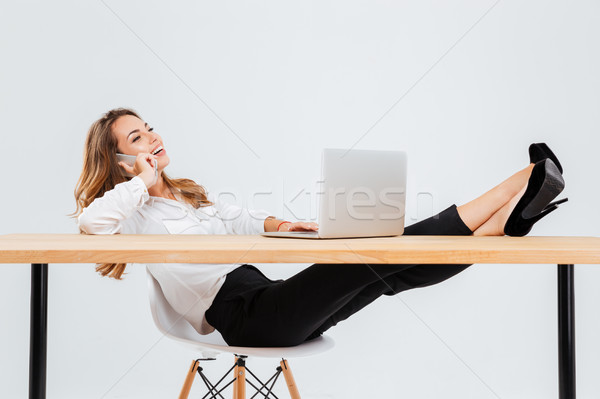 Cheerful young businesswoman using laptop and talking on cell phone Foto stock © deandrobot