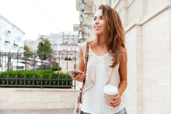 Girl walking on the street and drinking take away coffee Stock photo © deandrobot