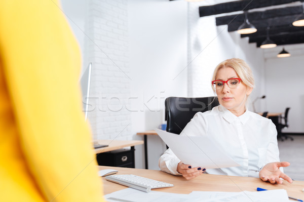 Cheerful beautiful mature businesswoman interviewing candidate for new position Stock photo © deandrobot
