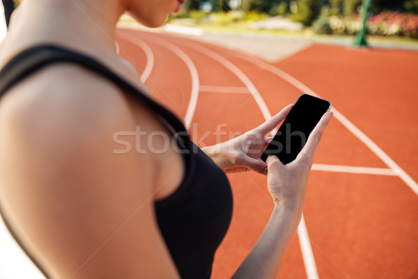 Cropped image of woman resting after run and using smartphone Stock photo © deandrobot