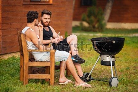 Two men sitting while preparing barbecue grill in park zone Stock photo © deandrobot
