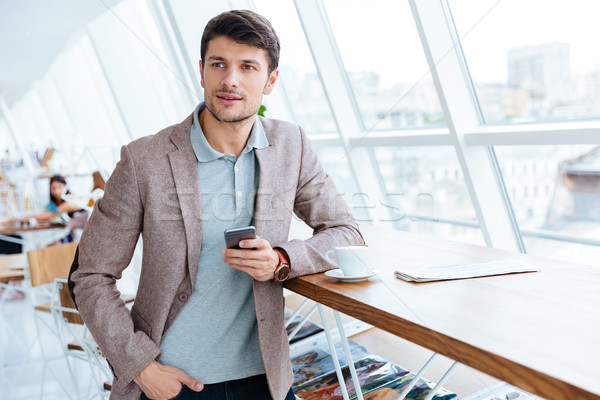 Man in jacket holding mobile phone while having lunch break Stock photo © deandrobot