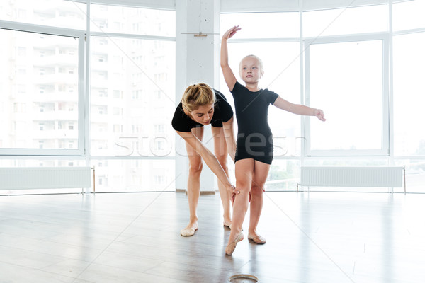Graceful little ballerina and her teacher dancing in ballet school Stock photo © deandrobot