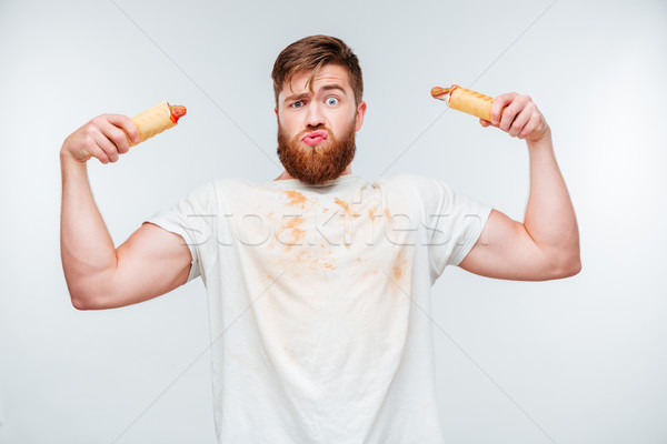Funny bearded man in filthy shirt holding to hotdogs Stock photo © deandrobot