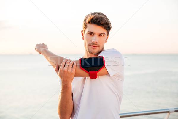 Confident young muscular man stretching his arms at the seaside Stock photo © deandrobot