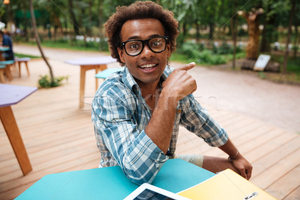 Cheerful african young man siting in cafe and pointing away Stock photo © deandrobot