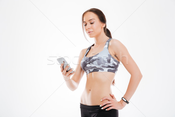 Aerobic woman with phone Stock photo © deandrobot