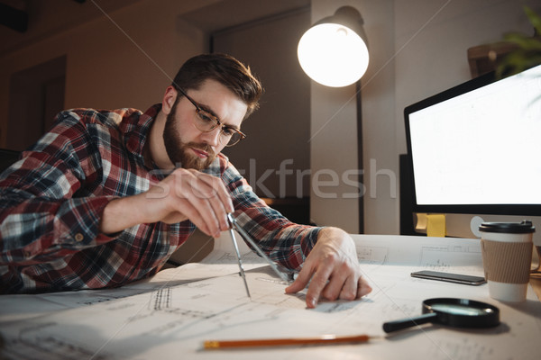 Serious bearded man in eyeglasses working over graph holding compass Stock photo © deandrobot