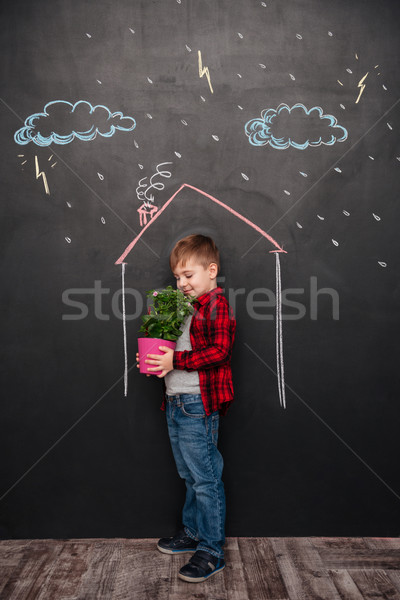 Kid standing in house on chalkboard holding flower and smelling Stock photo © deandrobot