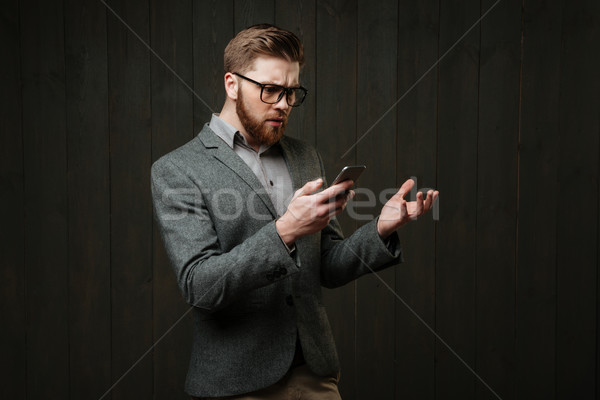 Surprised man in eyeglasses and casual suit holding mobile phone Stock photo © deandrobot