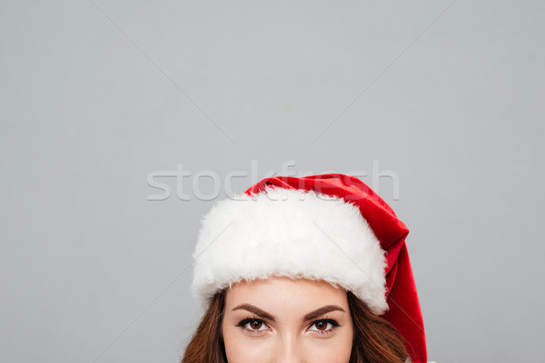 Closeup of young woman in red santa claus hat Stock photo © deandrobot
