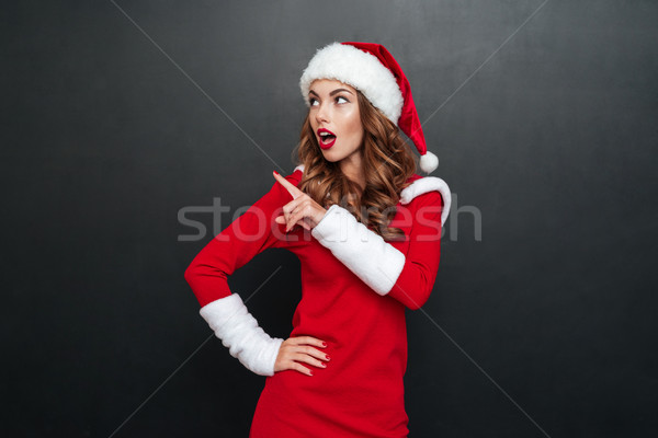 Surprised woman in christmas dress with finger point aside Stock photo © deandrobot