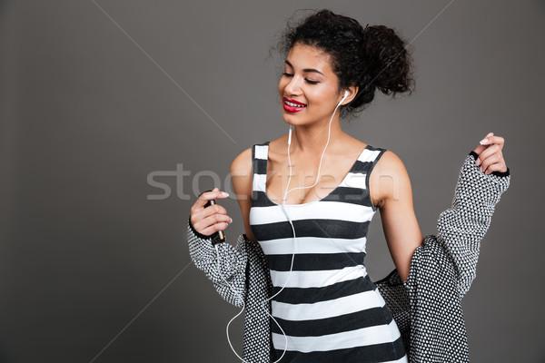 Mosolyog csinos nő zenét hallgat fülhallgató portré izolált Stock fotó © deandrobot