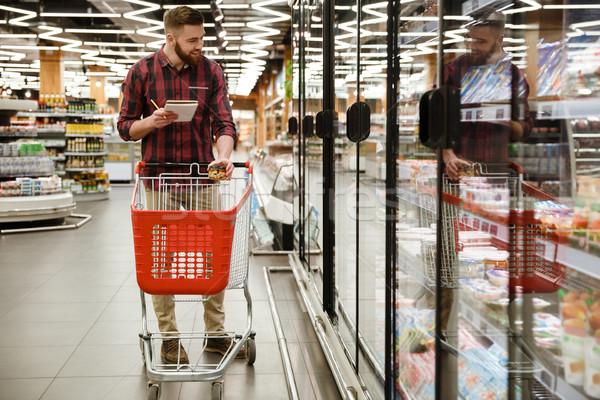 Vrolijk jonge man permanente supermarkt kiezen producten Stockfoto © deandrobot