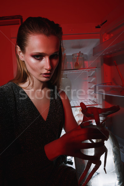 Vertical image of mystery woman holding jar with doll Stock photo © deandrobot