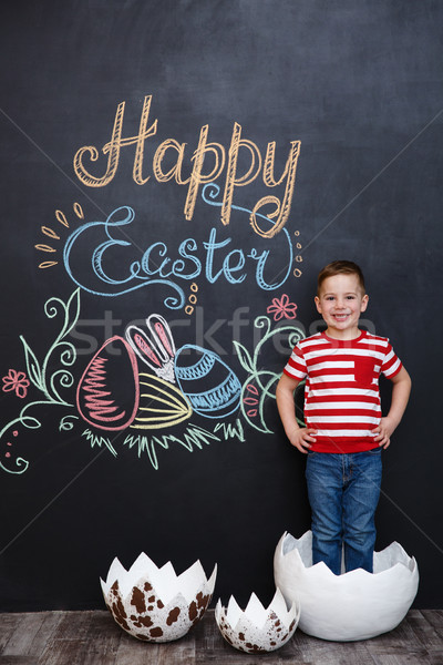 Happy little boy standing inside big cracked eggshell Stock photo © deandrobot