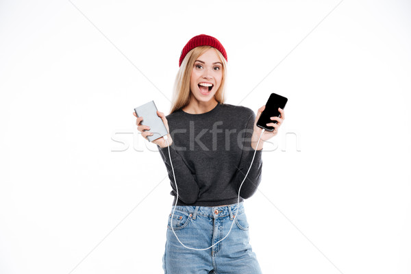 Woman in sweater holding power bank and smartphone Stock photo © deandrobot
