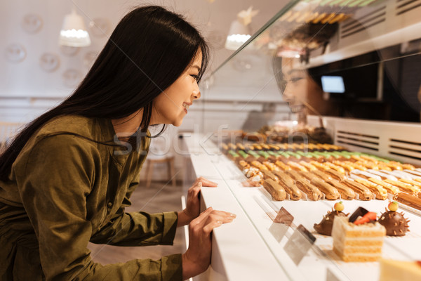 Cheerful asian young lady looking at sweeties. Stock photo © deandrobot
