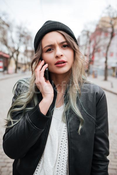 Verward jonge vrouw praten mobiele telefoon foto Stockfoto © deandrobot