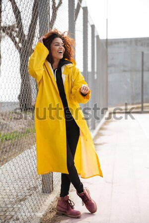 Happy african curly young lady walking and waving. Stock photo © deandrobot
