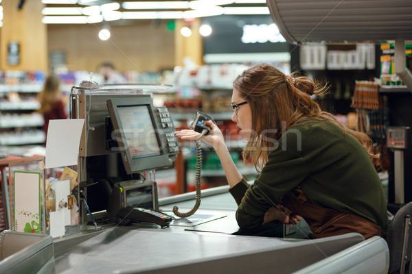 Confused cashier on workspace in supermarket shop. Stock photo © deandrobot