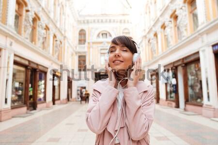 Menina rosa casaco ouvir música fones de ouvido fora Foto stock © deandrobot