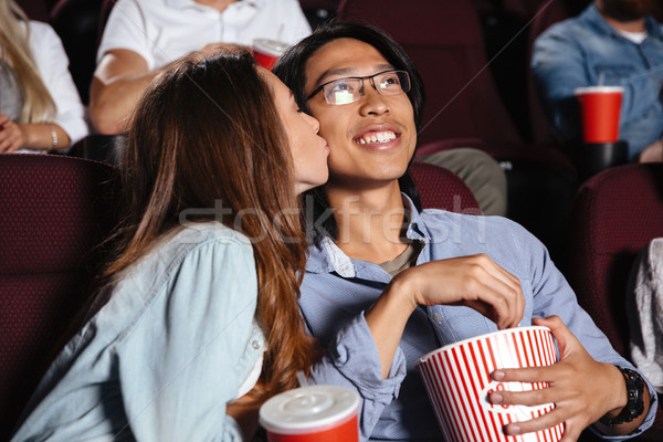 Loving couple sitting in cinema watch film and kissing Stock photo © deandrobot