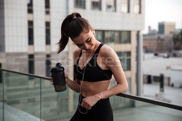 Pretty young sports woman standing with earphones Stock photo © deandrobot